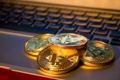 Foto guld- Bitcoins på bärbara datorn handelbegrepp av crypto valuta Arkivbild