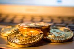 Foto guld- Bitcoins på bärbara datorn handelbegrepp av crypto valuta Arkivfoto