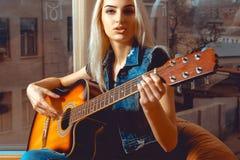 Foto horizontal de la mujer rubia joven con la guitarra en sus manos Fotos de archivo
