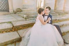 Foto horizontal de las manos del holdign de los recienes casados mientras que se sienta en las escaleras del edificio antiguo Fotos de archivo libres de regalías