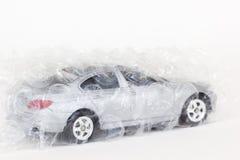 Foto horizontal de um brinquedo cinzento do carro com o invólucro com bolhas de ar do ar no branco fotos de stock