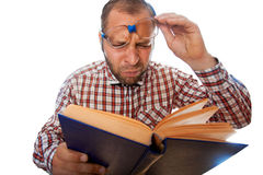 Foto horizontal del friki con vista pobre que lee un libro Fotografía de archivo