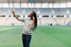 Foto horizontal del sportgirl afroamericano serio que toma el selfie en el fondo del estadio Fotos de archivo libres de regalías