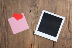 Foto inmediata con la nota y los corazones en blanco Foto de archivo