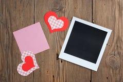 Foto inmediata con la nota y los corazones en blanco Imagen de archivo libre de regalías