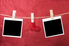 Foto inmediata en blanco y corazones rojos que cuelgan en la cuerda, tarjeta del día de San Valentín Fotos de archivo