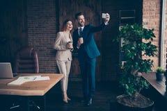 Foto integrale di dimensione corporea la sua signora di affari lui lui i suoi compagni del tipo tiene lo Smart Phone caldo dei br fotografia stock