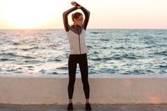 Foto integrale di giovane donna graziosa nell'usura di sport che fa stre Fotografia Stock