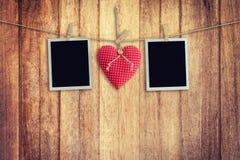 Foto istantanee in bianco e cuore rosso che appendono sul fondo di legno Fotografia Stock Libera da Diritti