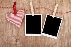 Foto istantanee in bianco e cuore rosso che appendono sulla corda da bucato Fotografie Stock Libere da Diritti