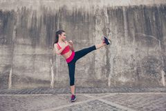 Foto lateral do perfil da morena atrativa, pontapé alto kickboxing foto de stock