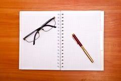 Foto lisa da configuração do bloco de notas, da pena e dos vidros isolados no branco Fotografia de Stock