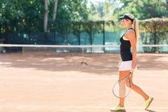 Foto llena del cuerpo del jugador de tenis de sexo femenino en la acción en un campo de tenis al aire libre Foto de archivo