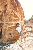 Foto llena-lengh de la muchacha rubia bonita con el pelo largo que presenta a la c?mara en la playa en fondo de la roca Ella llev foto de archivo