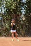 Foto llena vertical del cuerpo del jugador de tenis de sexo femenino rubio con la bola en la corte al aire libre Fotos de archivo