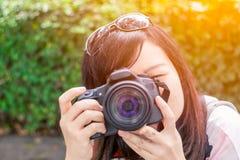 Foto longa do tiro do cabelo do preto asiático bonito da mulher com câmara digital fotografia de stock royalty free