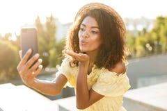 Foto luftkusses des Strohhutes der Frau 20s des tragenden Schlagund des nehmen selfie auf Smartphone stockbild