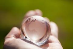 Foto macro do globo de vidro na mão humana Imagens de Stock Royalty Free