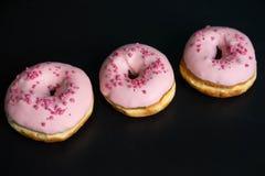 Foto med donuts och marshmallower på en svart bakgrund S?tsaker p? en m?rk bakgrund Rosa Donuts royaltyfria foton