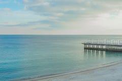 Foto med gult solljus av havet och den molniga himlen I vattnet är pir, som leder till den sandiga kusten arkivbild