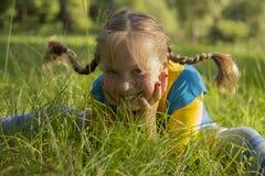 A foto Menina com as tranças engraçadas, sentando-se na grama Foto de Stock Royalty Free