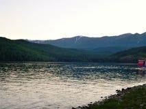 Foto met de achtergrond van meer Baikal in Rusland, rotsachtige oever en bergpieken op de horizon Stock Foto