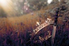 foto misteriosa y mágica de la corona y de la espada del rey del oro en el paisaje de maderas o del campo de Inglaterra con la ll foto de archivo