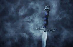 foto misteriosa y mágica de la espada de plata sobre fondo negro gótico con humo concepto medieval del período foto de archivo libre de regalías