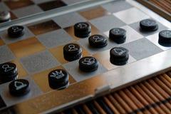 Foto mit einem Bild eines Schach Stahlbrettes und der Schachfiguren, Metallschachfiguren auf einem Schach Brett mit Reflexion Lizenzfreie Stockbilder