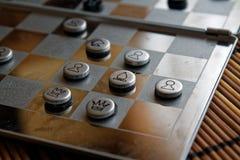 Foto mit einem Bild eines Schach Stahlbrettes und der Schachfiguren, Metallschachfiguren auf einem Schach Brett mit Reflexion Stockfotografie