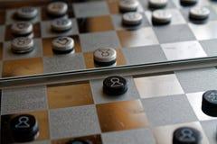 Foto mit einem Bild eines Schach Stahlbrettes und der Schachfiguren, Metallschachfiguren auf einem Schach Brett mit Reflexion Stockfotos