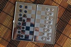 Foto mit einem Bild eines Schach Stahlbrettes und der Schachfiguren, Metallschachfiguren auf einem Schach Brett mit Reflexion Lizenzfreie Stockfotos