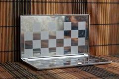 Foto mit einem Bild eines Stahlschach Brettes Metallbrett mit Reflexion Stockfotos