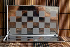 Foto mit einem Bild eines Stahlschach Brettes Metallbrett mit Reflexion Lizenzfreie Stockbilder