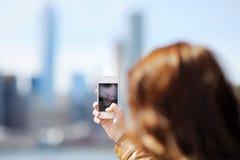 Foto mobile di presa turistica femminile dei grattacieli fotografia stock libera da diritti