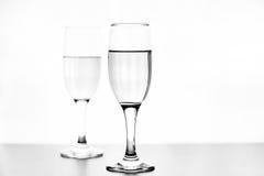 Foto monocromatica di champagne sulla tavola bianca su fondo bianco Fotografia Stock Libera da Diritti