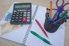 A foto mostra um close up da calculadora e do dinheiro do negócio em um papel fotografia de stock