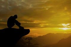Foto mostrada em silhueta Homem só que senta-se no penhasco fotografia de stock