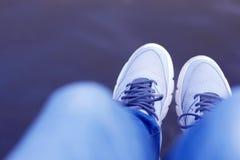 Foto: NadyaSo baumeln Füße über Wasser, Jeans, graue Turnschuhe, erste Person lizenzfreie stockfotos