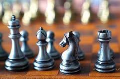 Foto no foco seletivo de uma placa de xadrez e de partes de xadrez do metal foto de stock royalty free