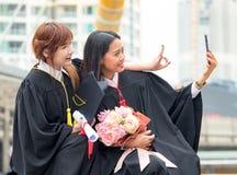 Foto nova do sorriso e do selfie do retrato da mulher dos pares em seu graduado foto de stock royalty free