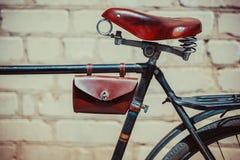 Foto oude uitstekende fiets, die zich dichtbij de bakstenen muur bevindt Sluit omhoog van een oud, uitgeput fietskader waarin lee Royalty-vrije Stock Foto's