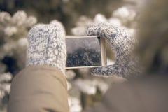 Foto på telefonen Varma tumvanten Förgrena sig av spruce armhåla Arkivfoton