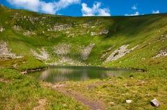 Foto panorâmico de um lago da montanha em um vale rochoso montanhoso Lago sereno Berbeneskul, Carpathians, Ucrânia foto de stock royalty free