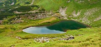 Foto panorâmico de um lago da montanha em um vale rochoso montanhoso Lago sereno Berbeneskul, Carpathians, Ucrânia fotografia de stock