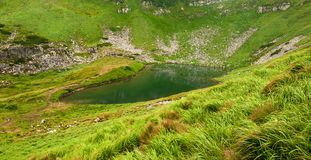Foto panorâmico de um lago da montanha em um vale rochoso montanhoso Lago sereno Berbeneskul, Carpathians, Ucrânia imagens de stock