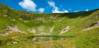 Foto panorâmico de um lago da montanha em um vale rochoso montanhoso Lago sereno Berbeneskul, Carpathians, Ucrânia imagem de stock