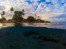 Foto partida con la isla tropical y el arrecife de coral subacuático Paisaje doble con el mar y el cielo Fotos de archivo