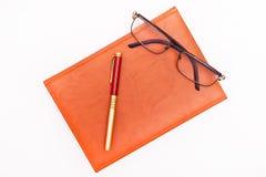 Foto piana di disposizione del blocco note, della penna e dei vetri isolati sul bianco Immagini Stock