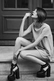 Foto piena all'aperto monocromatica del corpo di giovane bella signora alla moda che posa sulle scale Vestiti alla moda d'uso di  fotografie stock
